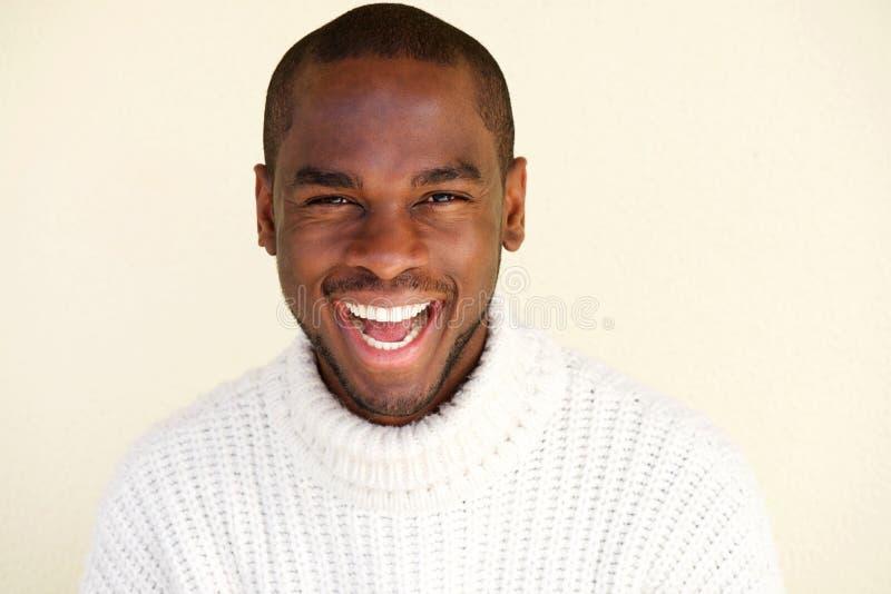 Sluit omhoog de vrolijke Afrikaanse Amerikaanse mens die tegen lichte achtergrond lachen stock afbeelding