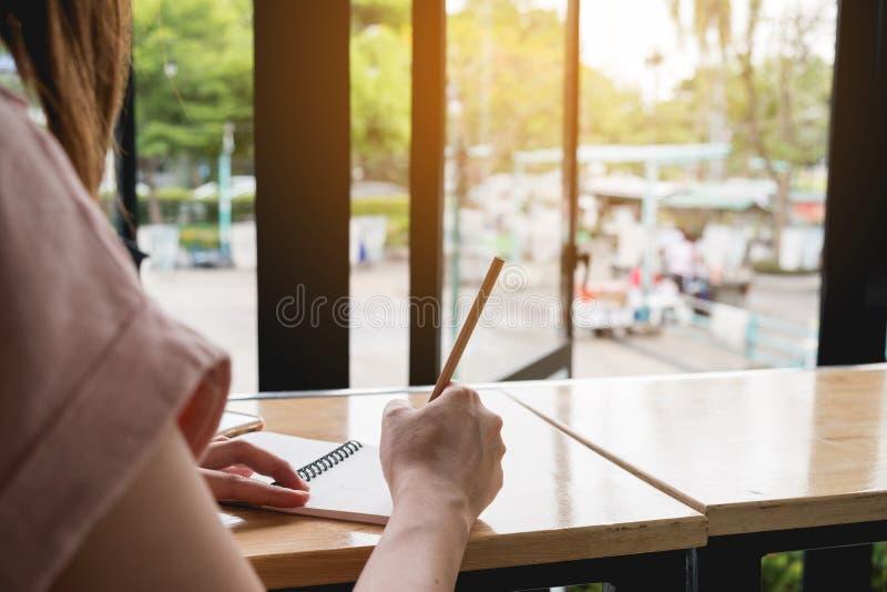 Sluit omhoog De vrouwenhand schrijft op blocnote met potlood naast venster stock afbeeldingen