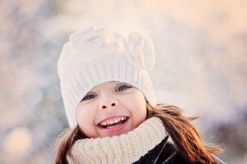 Sluit omhoog de winterportret van aanbiddelijk gelukkig kindmeisje in sneeuwbos stock fotografie