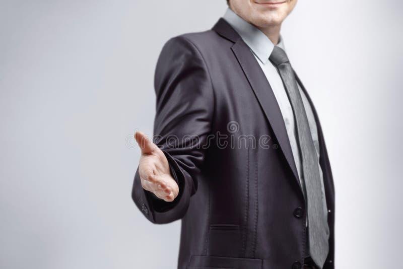 Sluit omhoog de zakenman breidt zijn hand voor groet uit Geïsoleerd op grijze achtergrond stock afbeelding
