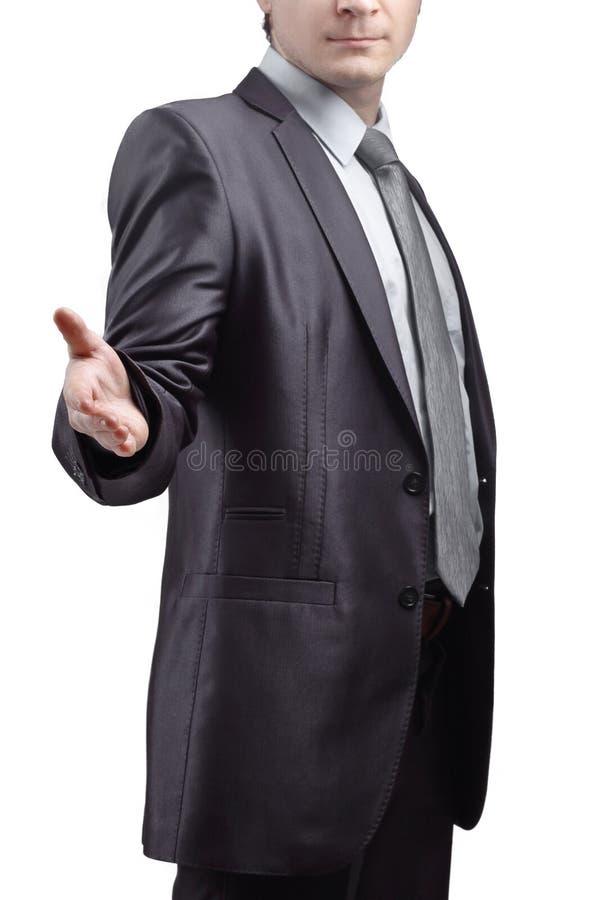 Sluit omhoog de zakenman breidt zijn hand voor groet uit Ge?soleerd op grijze achtergrond royalty-vrije stock afbeelding