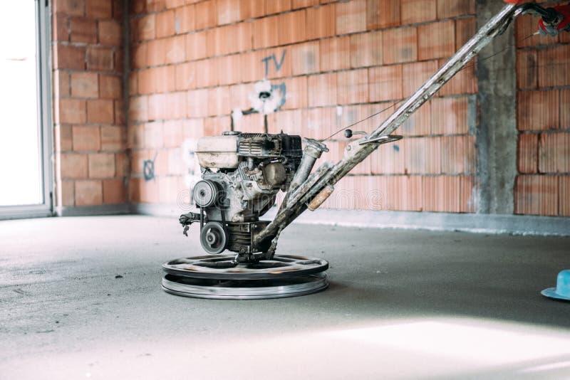 Sluit omhoog details van bouwvakker die concrete screed met de machine van de machtstroffel beëindigen stock afbeeldingen