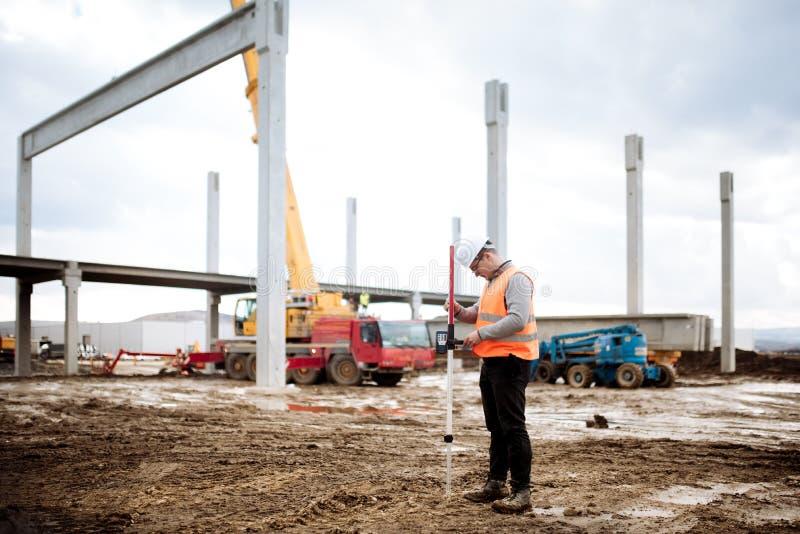 Sluit omhoog details van bouwwerf, industriële civiel-ingenieur die met geprefabriceerde cementpijlers werken stock fotografie