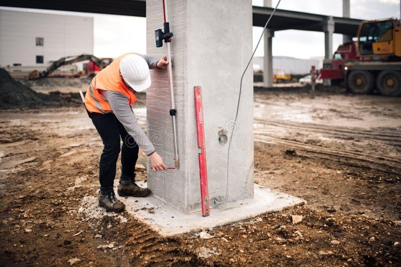 Sluit omhoog details van werkende onderzoekende ingenieur op het landmeterswerk bij bouwwerf stock afbeeldingen