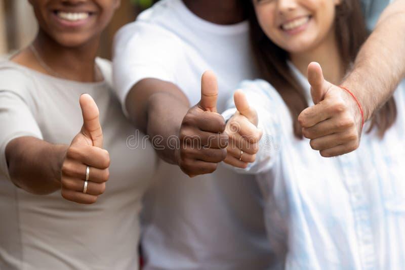 Sluit omhoog diverse mensen die duimen tonen stock afbeeldingen