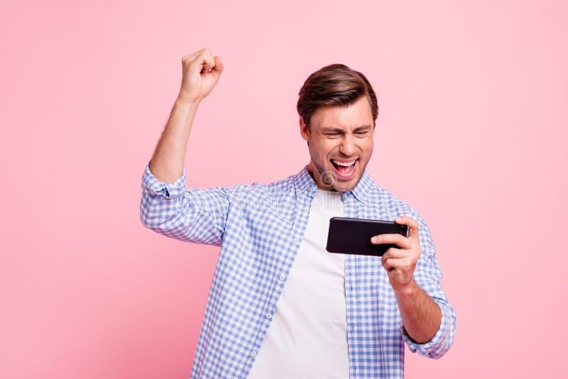 Sluit omhoog donkerbruine foto van het mooie verbazen hij hem zijn knappe greep nieuwe telefoon testend het videospelletjevuist i stock foto