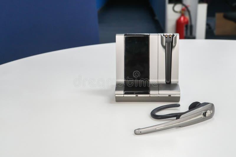 Sluit omhoog draadloze hoofdtelefoon op bureau voor mededeling en globale conferentievraag royalty-vrije stock afbeelding
