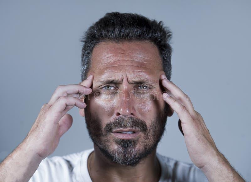 Sluit omhoog dramatisch portret van de jonge aantrekkelijke bezorgde en gedeprimeerde mens in pijn met handen op zijn hoofd lijde royalty-vrije stock afbeeldingen