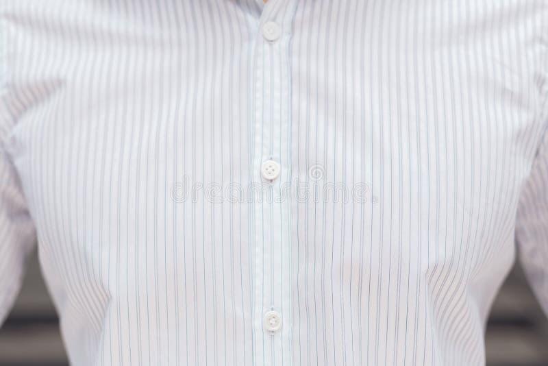 Sluit omhoog een deel van een wit bedrijfsoverhemd op een mens stock foto