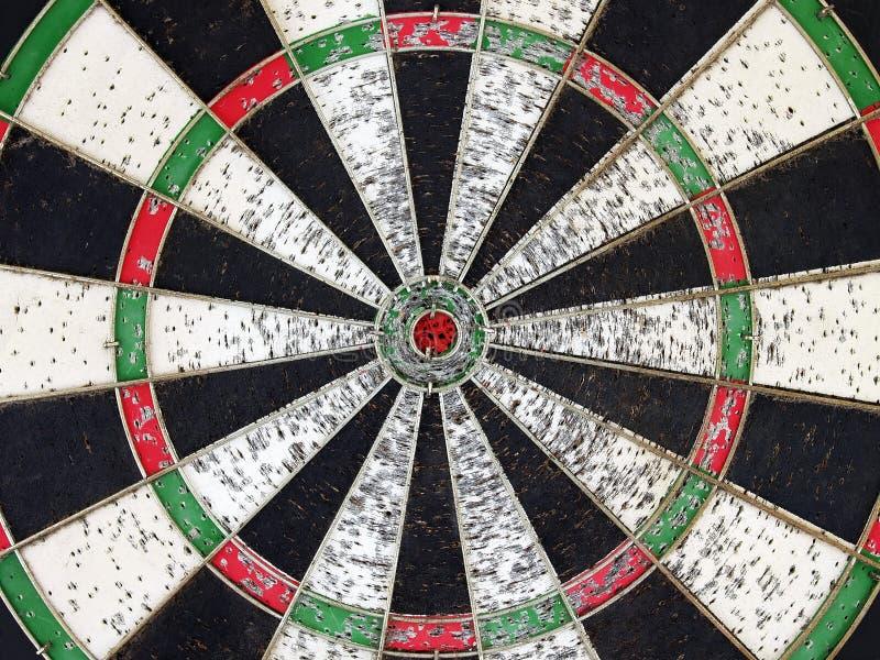 Sluit omhoog een deel van ouwelijk kleurrijk houten dartboard met het oogdoel van rode kleurenstieren en poreus veroorzaakt door  royalty-vrije stock afbeeldingen