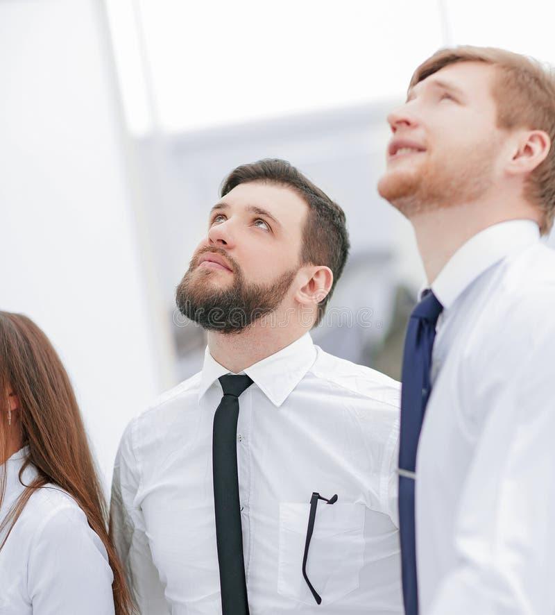 Sluit omhoog een groep bedrijfsmensen bekijkt omhoog een exemplaar van de ruimte stock foto