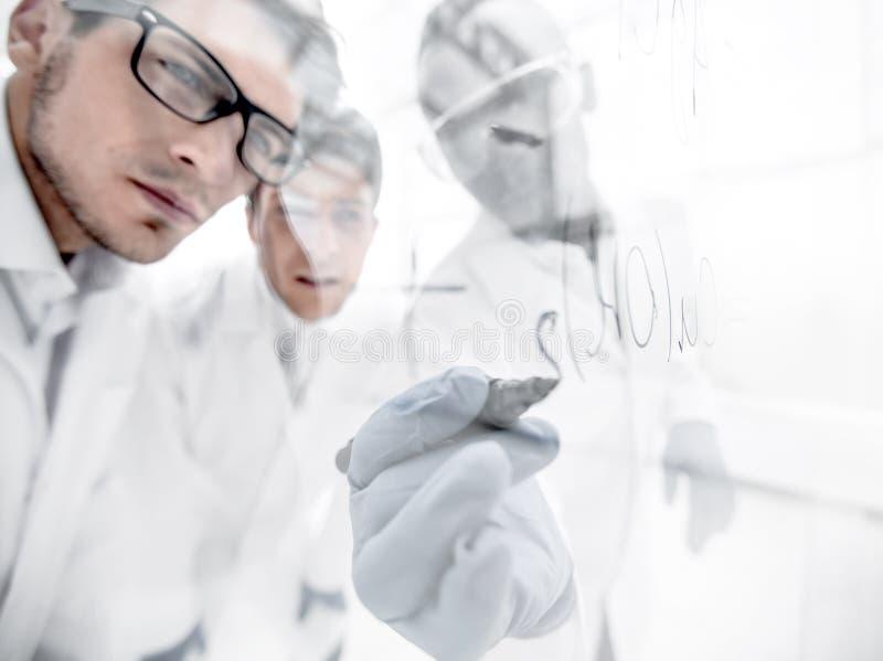 Sluit omhoog een groep wetenschappers die de formule op een glasraad registreren royalty-vrije stock foto's