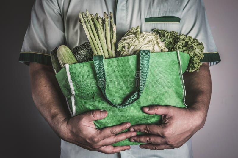 Sluit omhoog een hand houdend de groene kruidenierswinkelzak van organisch g mengde royalty-vrije stock afbeelding