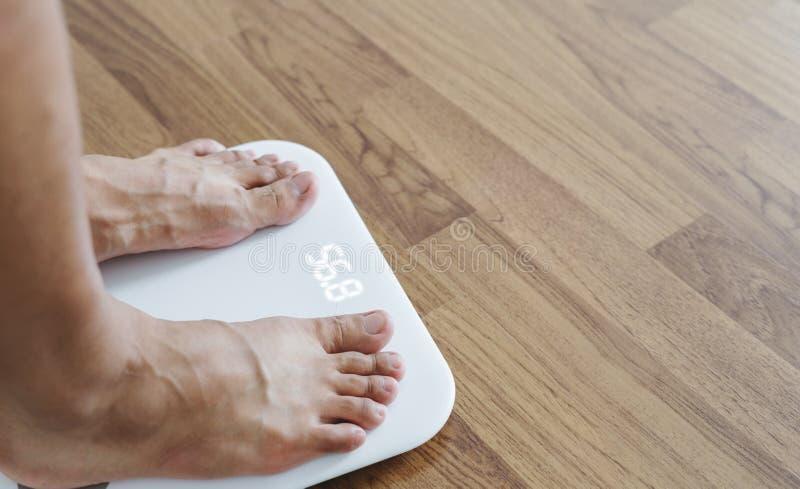 Sluit omhoog een mensenvoeten op lichaamsschaal controlerend lichaamsgewicht, op dieet zijnd en verlies gewichtsconcept stock foto