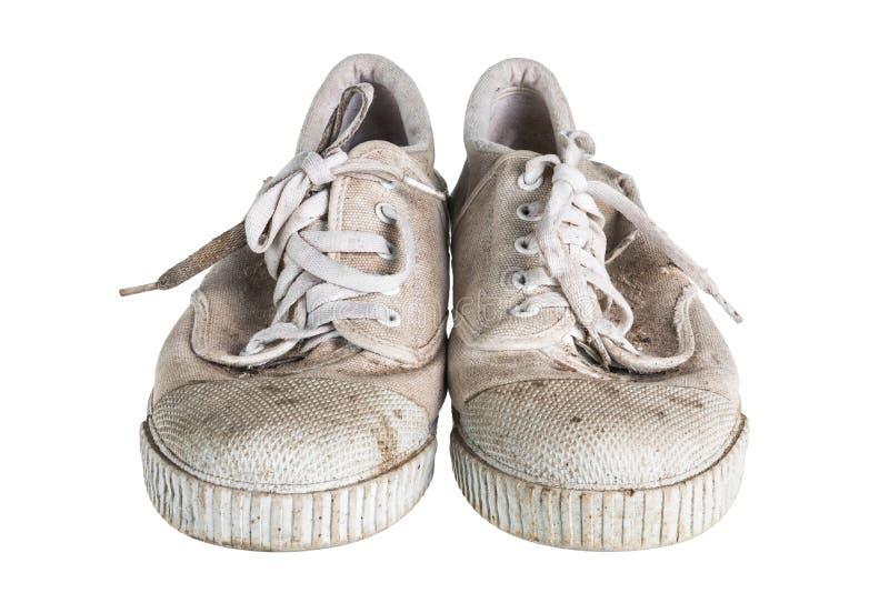 Sluit omhoog een paar vuile die tennisschoenen op witte achtergrond wordt geïsoleerd stock foto