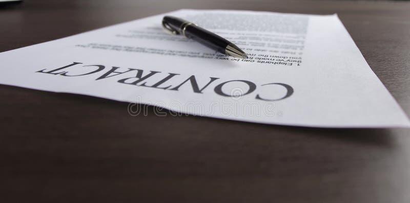Sluit omhoog een pen en een blad met het ondertekende contract stock fotografie