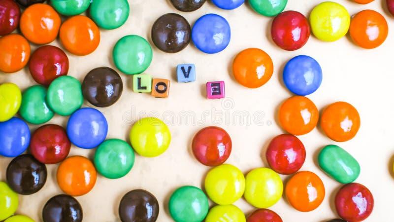 Sluit omhoog een stapel van kleurrijk met chocolade bedekt suikergoed De achtergrond van de chocolade Snoepje en liefdeteken stock afbeelding