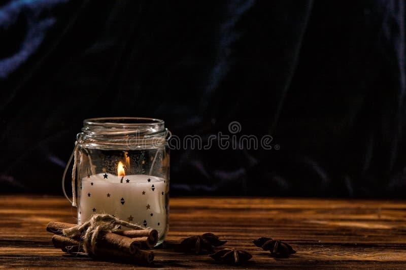 Sluit omhoog Een witte kaars in een transparante glaskruik brandt, kaneel, wordt de anijsplant opgemaakt rond het Rustieke bruine royalty-vrije stock afbeelding