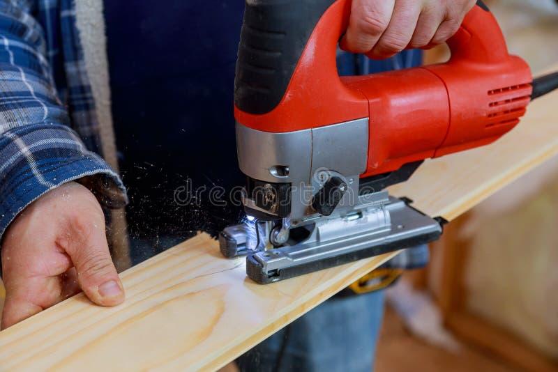 Sluit omhoog elektrische figuurzaag snijdend een stuk van hout royalty-vrije stock fotografie