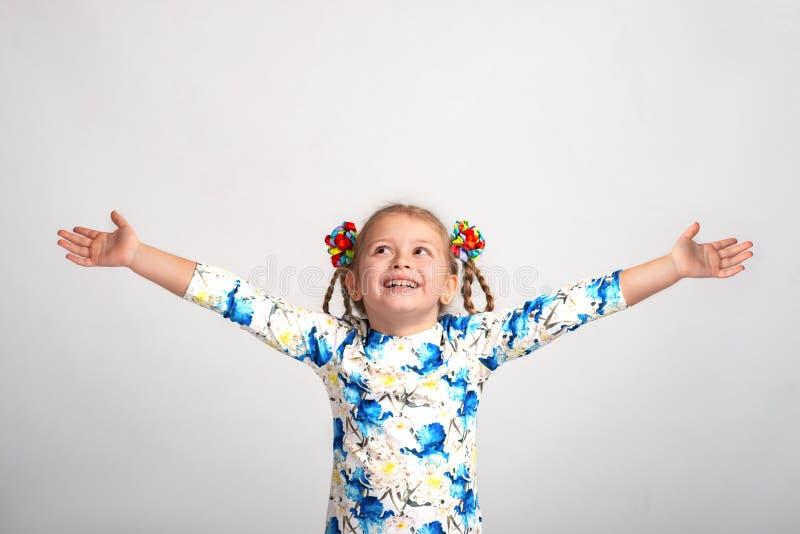 Sluit omhoog emotioneel portret van jong blonde glimlachend meisje die kleurenoverhemd met twee vlechten op grijze achtergrond in stock afbeeldingen