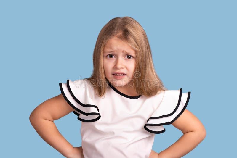 Sluit omhoog emotioneel portret van jong blondemeisje op blauwe achtergrond in studio Zij houdt haar handen bij de taille en is royalty-vrije stock afbeeldingen