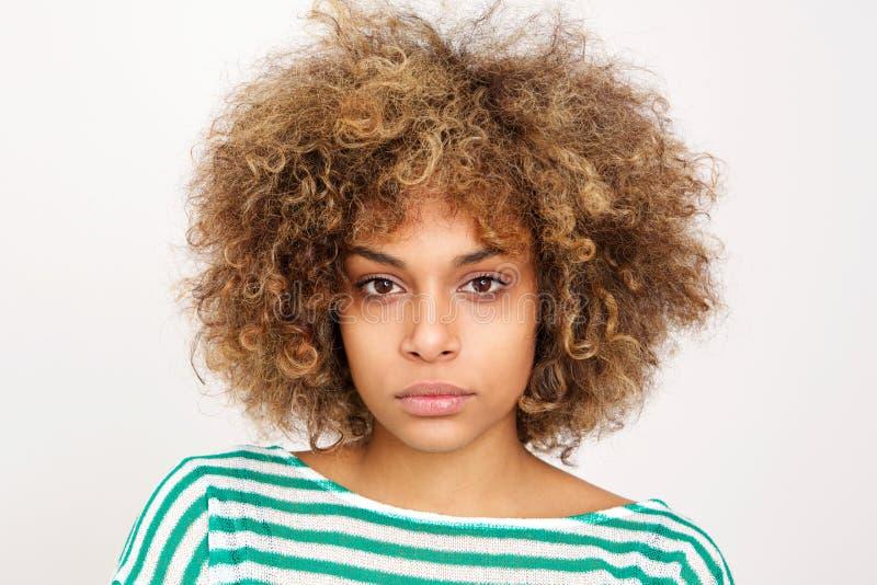 Sluit omhoog ernstige jonge Afrikaanse Amerikaanse vrouw tegen witte achtergrond royalty-vrije stock afbeelding
