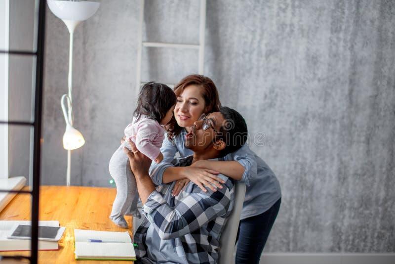 Sluit omhoog foto gelukkige moeder en vader die pret met hun mooi jong geitje hebben stock afbeelding