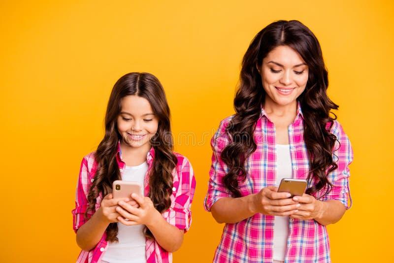 Sluit omhoog foto het mooie bruine haired kleine mamma weinig dochter telefoonslezer schrijft sms gekregen goed nieuws wijdde royalty-vrije stock afbeelding