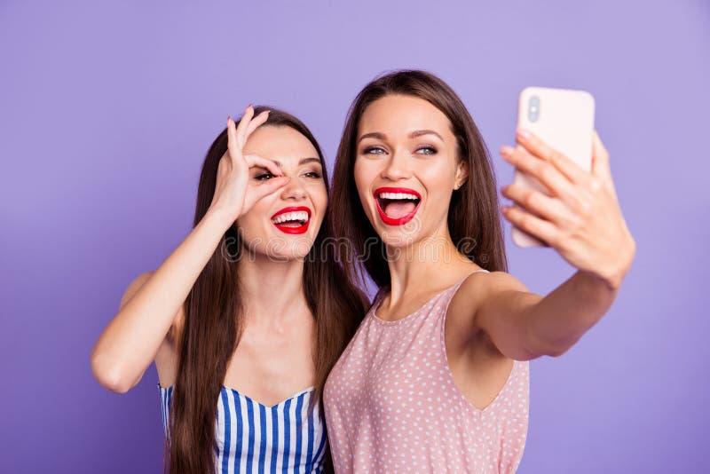 Sluit omhoog foto twee mooie funky zij haar van de de telefoonsmartphone van modellendames de handwapen maken selfies toothy rood royalty-vrije stock foto's