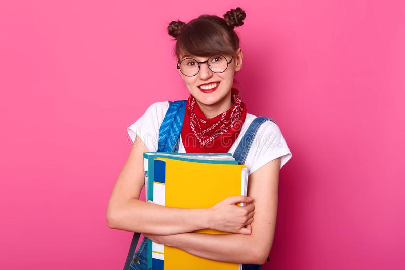 Sluit omhoog foto van gelukkige knappe die student met document omslag op rooskleurige achtergrond wordt geïsoleerd, die t-shirt  stock foto