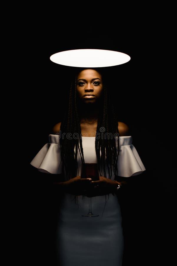 Sluit omhoog foto van het charmeren, wat betreft, offerte, mooie Afrikaanse vrouw status onder helder licht en het bekijken royalty-vrije stock afbeelding