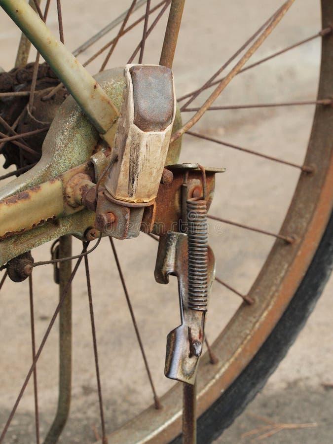 Sluit omhoog foto van oude, vuile en roestige fietskettingen, tand en voetpin bij achterwiel stock afbeelding