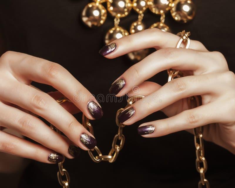 Sluit omhoog fotohanden met gouden manicureholding royalty-vrije stock fotografie