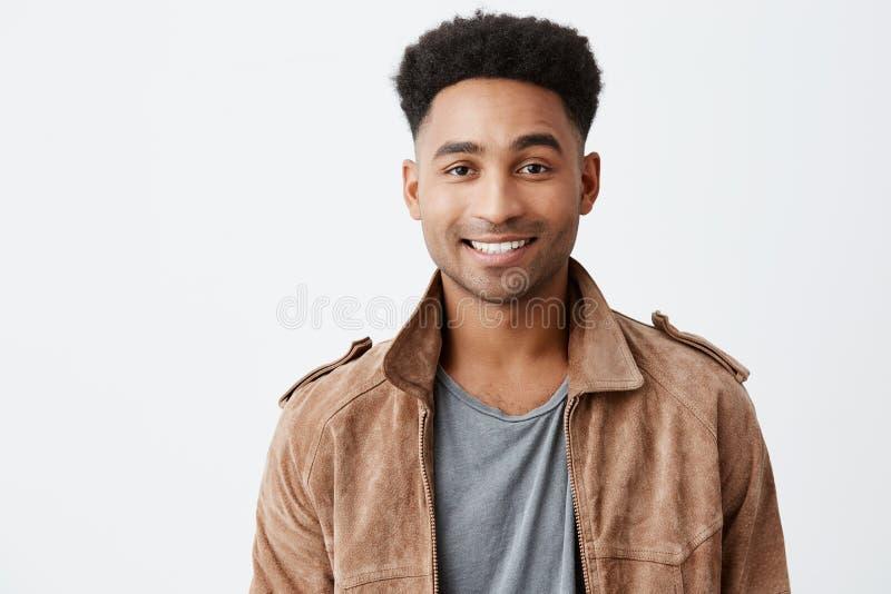 Sluit omhoog geïsoleerd portret van jonge donker-gevilde aantrekkelijke kerel met afrokapsel in grijze t-shirt onder bruin jasje stock foto