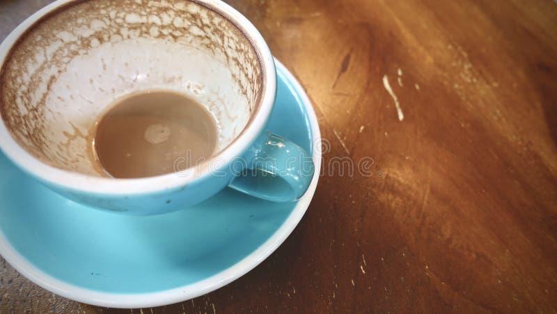 Sluit omhoog, gebeëindigde kop van hete cappuccino of hete lattekoffie met resterende lattekunst, gezet op natuurlijke bruine hou royalty-vrije stock afbeelding