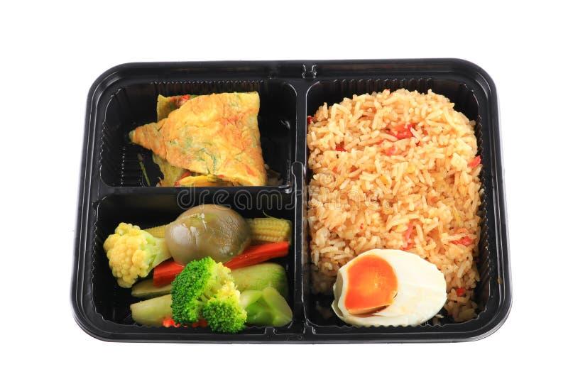 Sluit omhoog gebraden die rijst met ei en groenten in lunchdoos op witte achtergrond wordt geplaatst stock afbeelding