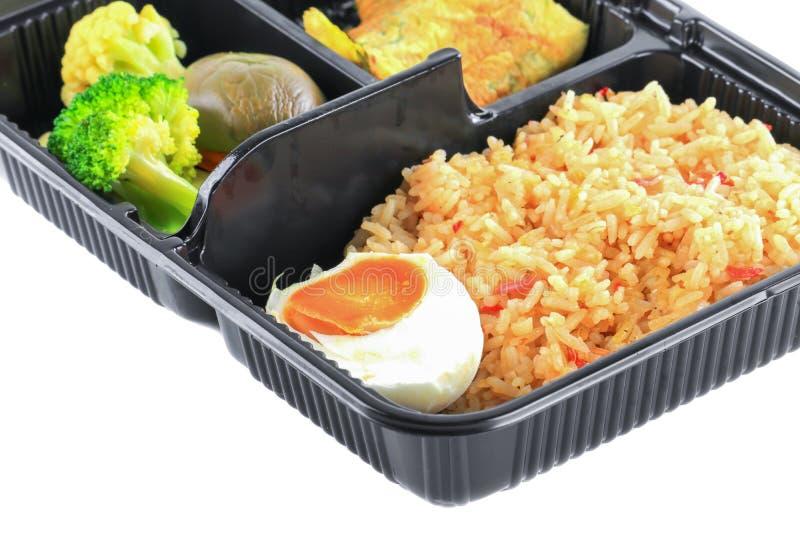 Sluit omhoog gebraden die rijst met ei en groenten in lunchdoos op witte achtergrond wordt geplaatst royalty-vrije stock afbeeldingen