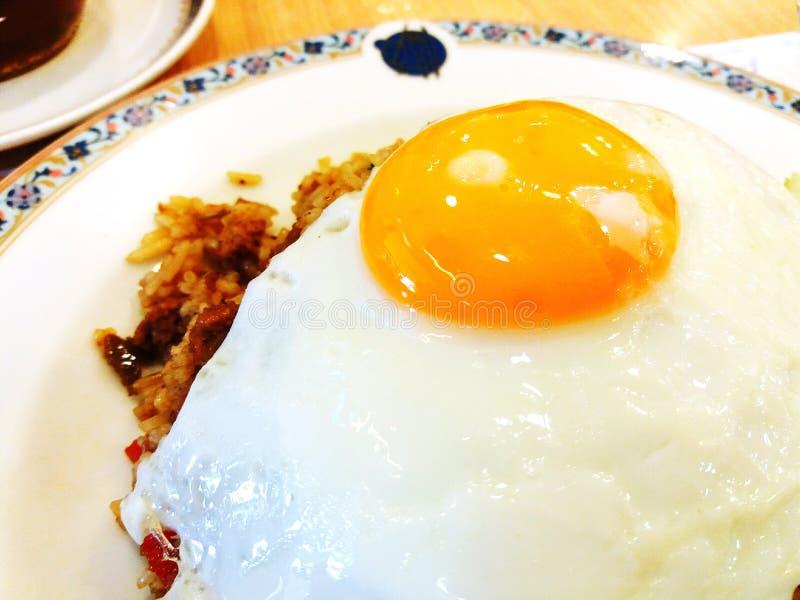 Sluit omhoog gebraden ei op de gebraden rijst met fijngehakt varkensvlees in witte plaat stock fotografie