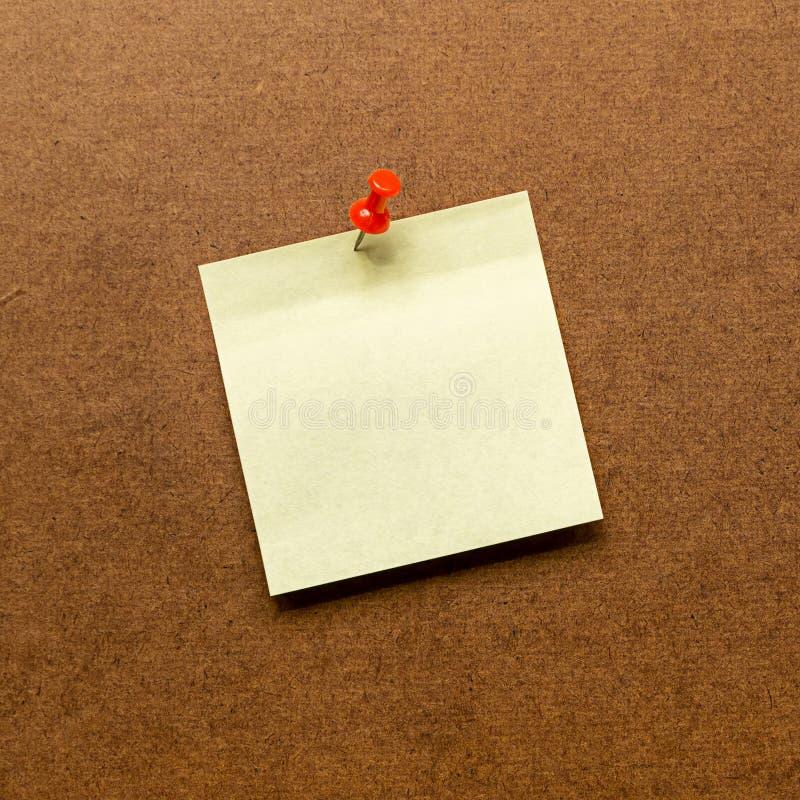 Sluit omhoog geel postnotadocument op de houten raad stock foto