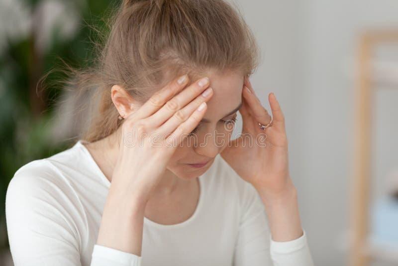 Sluit omhoog gefrustreerde vrouwenzitting op het werk stock foto