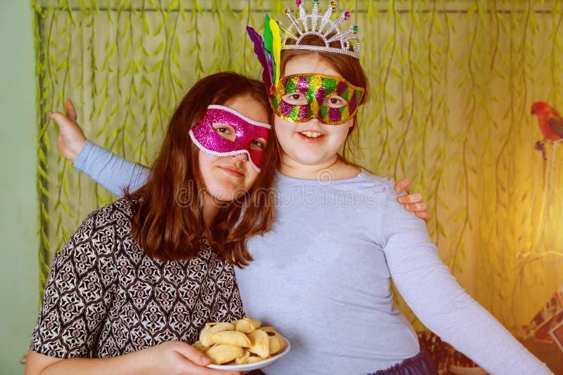 Sluit omhoog Geluk van pret en de gelukkige uitdrukkingen in Feestelijke Carnaval-Maskers met hamantaschen koekjes of hamans oren stock fotografie