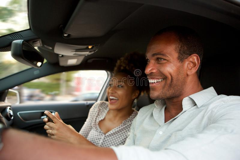 Sluit omhoog gelukkig Afrikaans Amerikaans paar in het snelle auto glimlachen stock foto