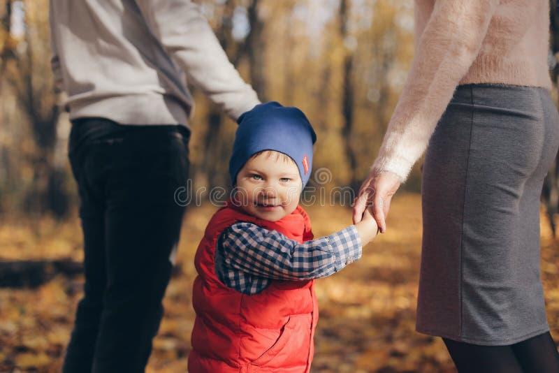 Sluit omhoog gelukkig portret van weinig jongen in blauw GLB die zijn oudershanden houden in het park openlucht stock fotografie