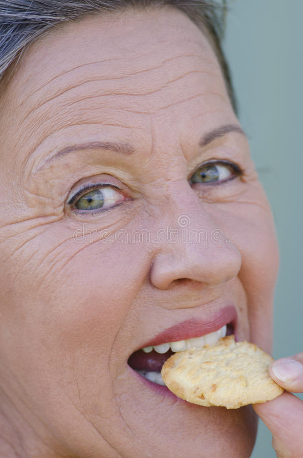 Sluit omhoog gelukkige vrouw bijtend zoete koekjessnack royalty-vrije stock afbeelding
