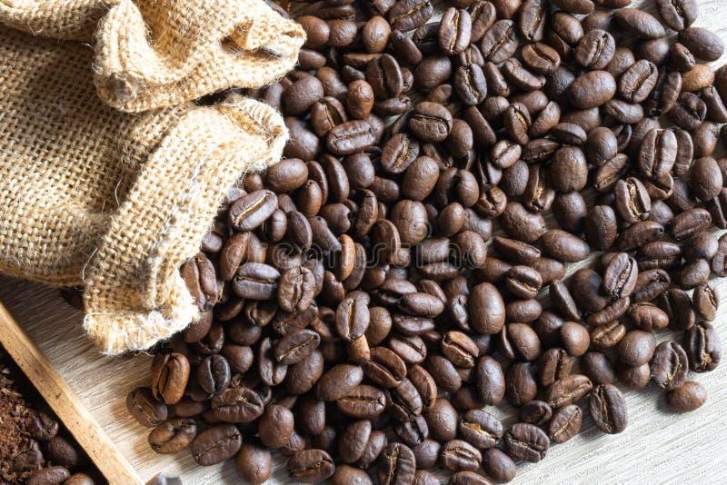 Sluit omhoog geroosterde koffiebonen in kleine zak op houten lijst stock fotografie