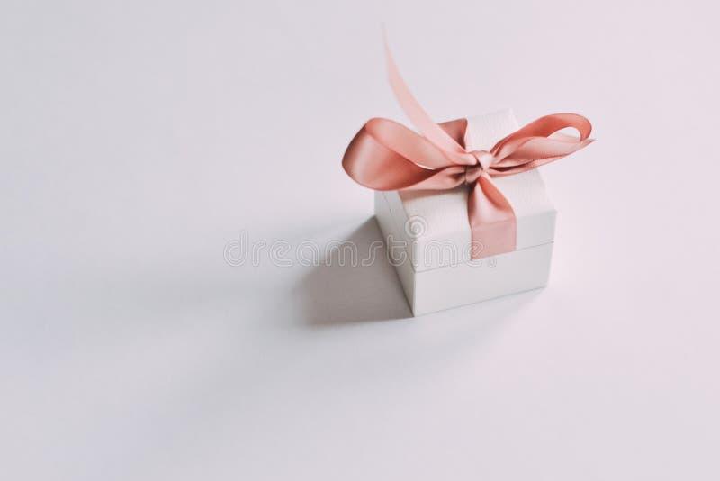 Sluit omhoog geschoten een kleine gift die met roze lint wordt verpakt stock afbeeldingen