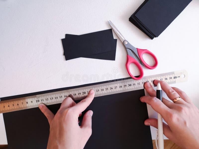 Sluit omhoog geschoten - professionele vrouwendecorateur, ontwerper het werken met kraftpapier-document en het maken van envelop  royalty-vrije stock fotografie