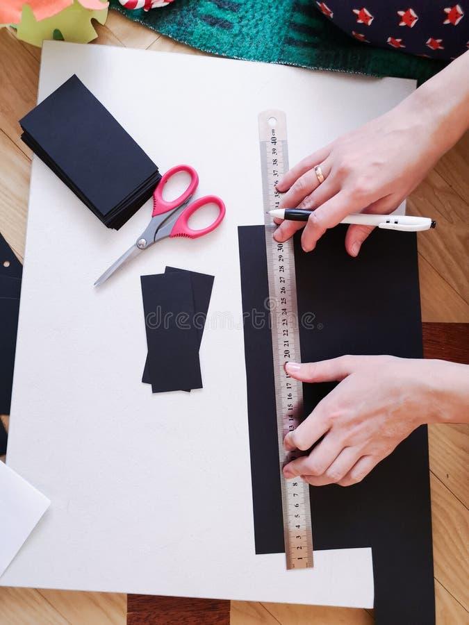 Sluit omhoog geschoten - professionele vrouwendecorateur, ontwerper het werken met kraftpapier-document en het maken van envelop  stock afbeelding