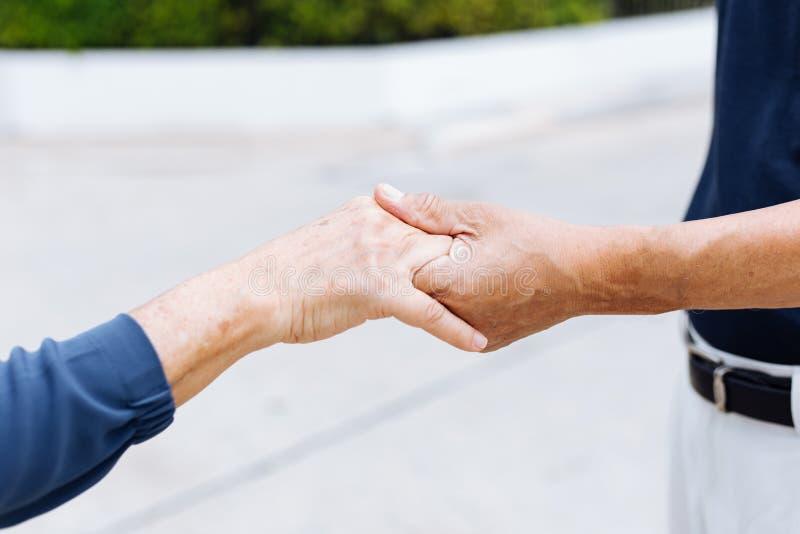 Sluit omhoog geschoten van de bejaarde hogere handen van de paarholding en het steunen met elkaar stock afbeelding