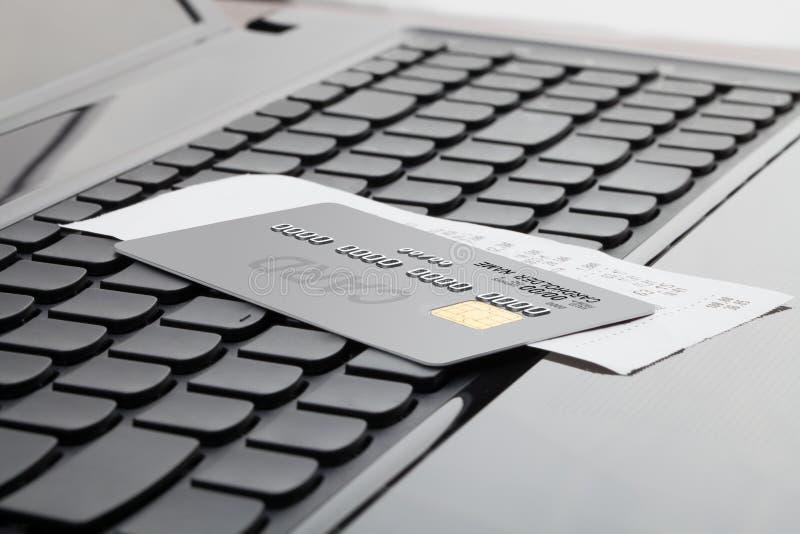 Sluit omhoog geschoten van een creditcard en een ontvangstbewijs over computertoetsenbord als symbool van online het winkelen stock foto's